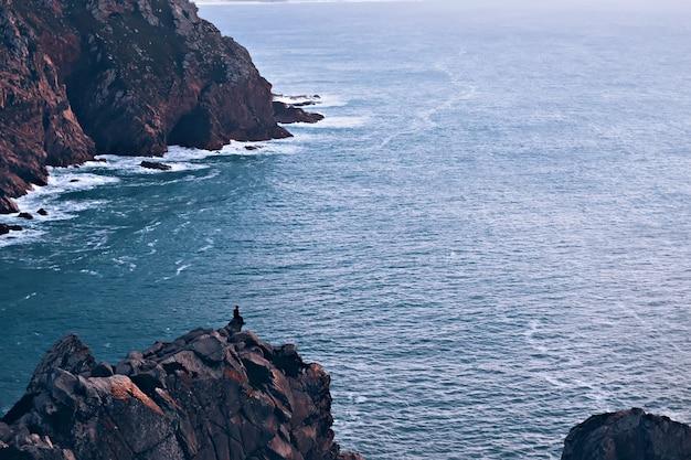Osoba siedzi na skałach i cieszy się widokiem na ocean