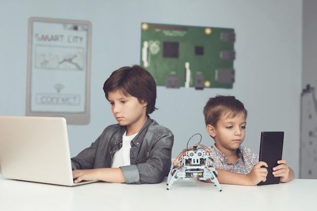 Osoba siedzi za laptopem, druga z tabletem.