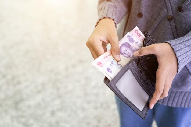 Osoba sprawdza banknoty w czarnym portflu