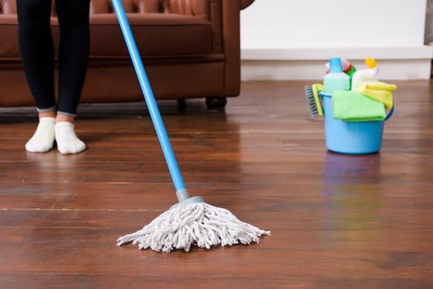 Osoba sprzątająca drewnianą podłogę w domu