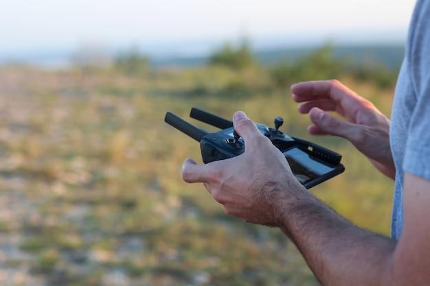 Osoba sterująca dronem za pomocą pilota