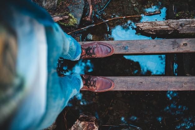 Osoba stojąca na drewnianym moście