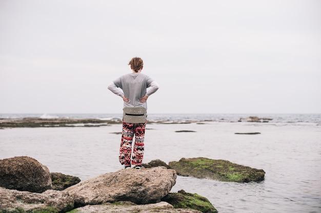 Osoba stojąca na omszałych skałach na zbiorniku wodnym