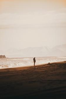 Osoba stojąca na piaszczystej plaży z czystym, białym niebem