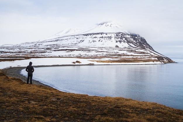Osoba stojąca na polu otoczonym morzem i skałami pokrytymi śniegiem na islandii