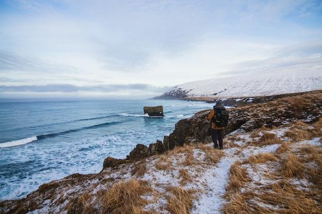 Osoba stojąca na wzgórzach pokrytych śniegiem otoczonych morzem na islandii