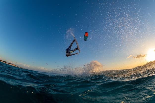 Osoba surfująca i latająca jednocześnie ze spadochronem w kitesurfingu. bonaire, karaiby