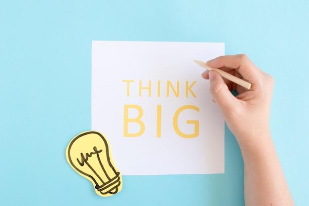 Osoba trzyma barwiony ołówka pisać tekst myśli dużą na białym papierze nad błękitnym tłem