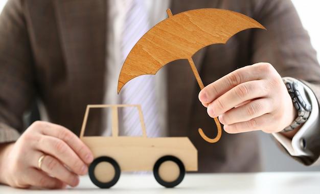 Osoba trzyma drewniany parasol nad samochodem