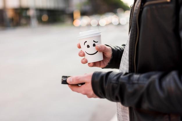 Osoba trzyma kubek i smartphone