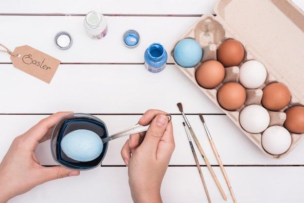 Osoba trzyma łyżkę z jajkiem nad szkłem z farbą