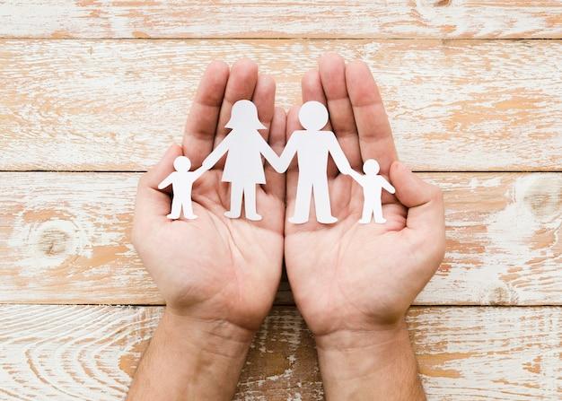 Osoba trzyma papierową rodzinę w rękach