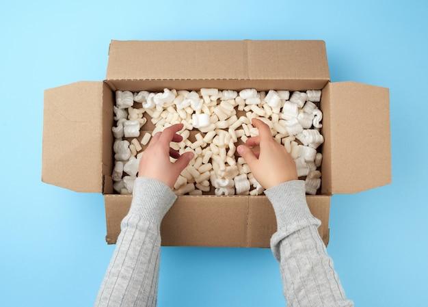 Osoba trzyma puste otwarte pudełko z brązowego kartonu z wypełnieniem piankowym