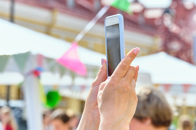 Osoba trzyma smartfon na ulicy i robi zdjęcie.