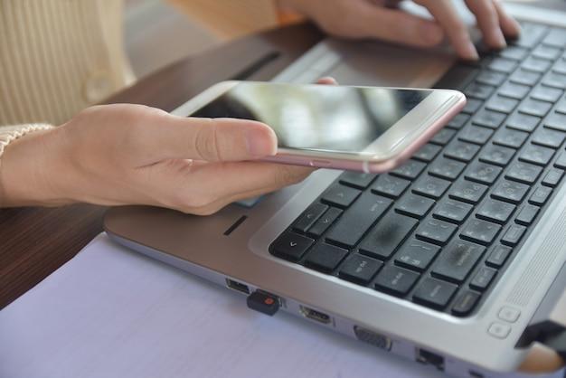 Osoba trzyma telefon komórkowy i korzysta z laptopa