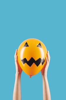 Osoba trzymająca balon z przerażającą twarzą
