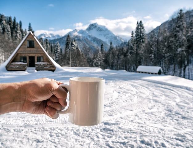 Osoba trzymająca biały porcelanowy kubek w zaśnieżone góry w słoneczny zimowy dzień.