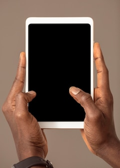 Osoba trzymająca cyfrowy tablet w pozycji pionowej