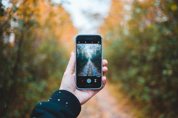 Osoba trzymająca czarny smartfon z włączoną aplikacją aparatu