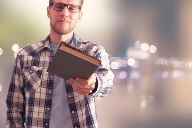 Osoba trzymająca i dająca książkę, dzieli się prezentem i wiedzą
