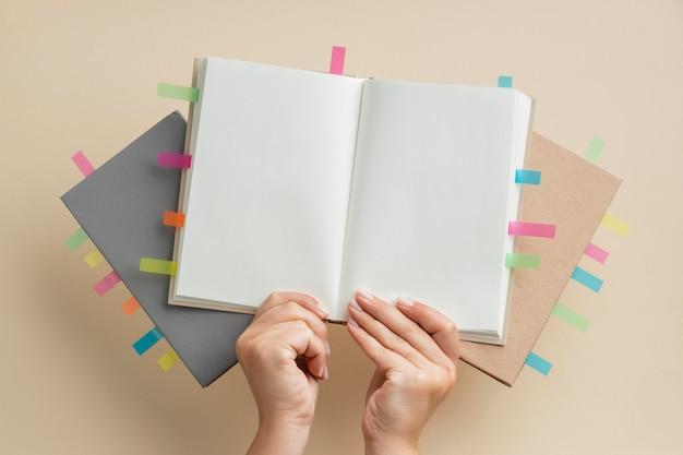 Osoba trzymająca książki z naklejkami kolorowe przypomnienia
