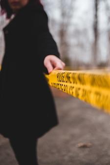 Osoba trzymająca linię policyjną i nie wchodząca w linię