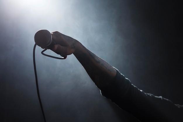 Osoba trzymająca mikrofon na scenie