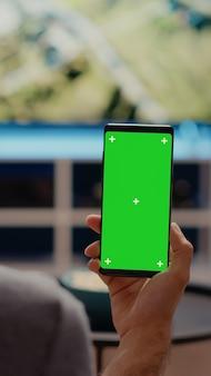 Osoba trzymająca pionowo telefon komórkowy z zielonym ekranem