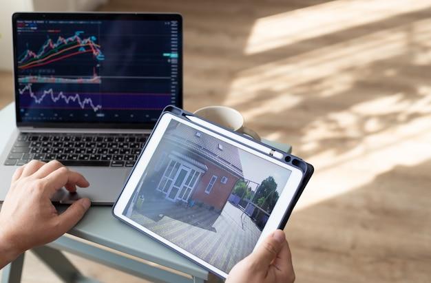 Osoba trzymająca się za ręce trzymająca cyfrowy tablet z kamerą bezpieczeństwa w domu i pracująca na laptopie freelance home office concept