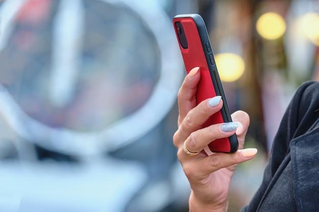 Osoba trzymająca smartfon w rękach podczas spaceru po ulicy.