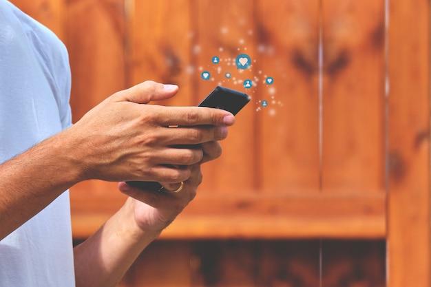 Osoba trzymająca smartfon z aktywnością w sieciach społecznościowych, subskrybenci, polubienia, wiadomości.