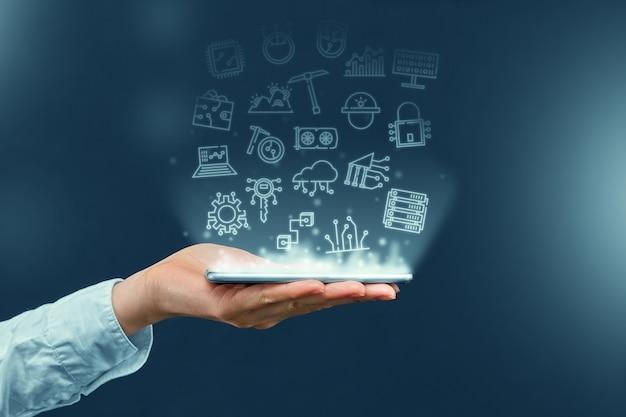 Osoba trzymająca smartfon z projekcją ikon biznesowych kryptowalut