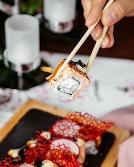 Osoba trzymająca sushi z laskami