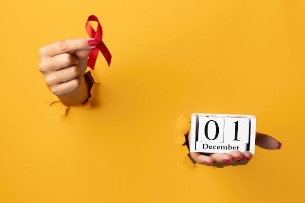 Osoba trzymająca symbol wstążki światowego dnia pomocy z datą wydarzenia