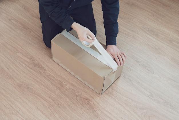 Osoba trzymająca taśmę i pudełko do pakowania kartonu wysyła i dostarcza przesyłkę