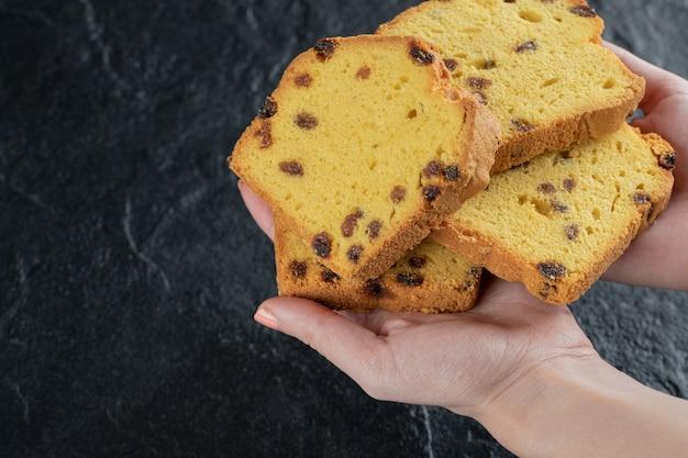Osoba trzymająca w dłoni plasterki ciasta sułtanki