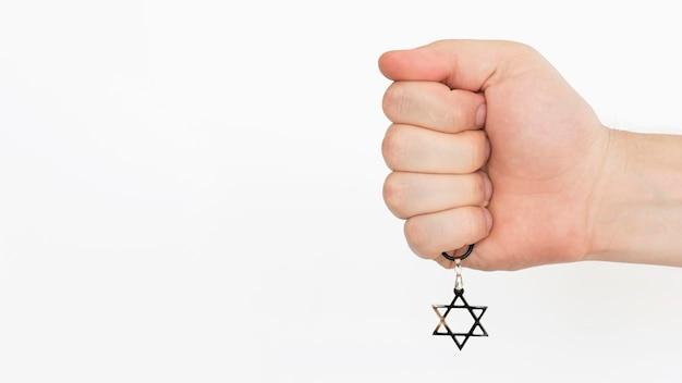 Osoba trzymająca w dłoni wisiorek z gwiazdą dawida