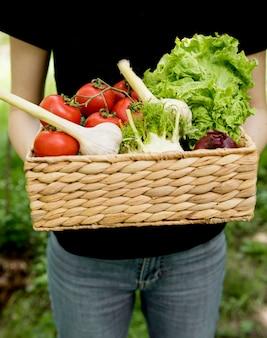 Osoba trzymająca wiadro z warzywami