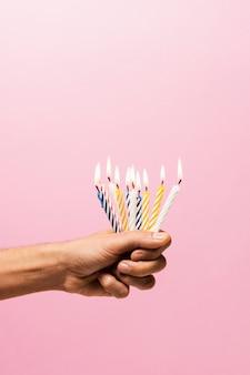 Osoba trzymająca zapalone świeczki na urodzinowym torcie