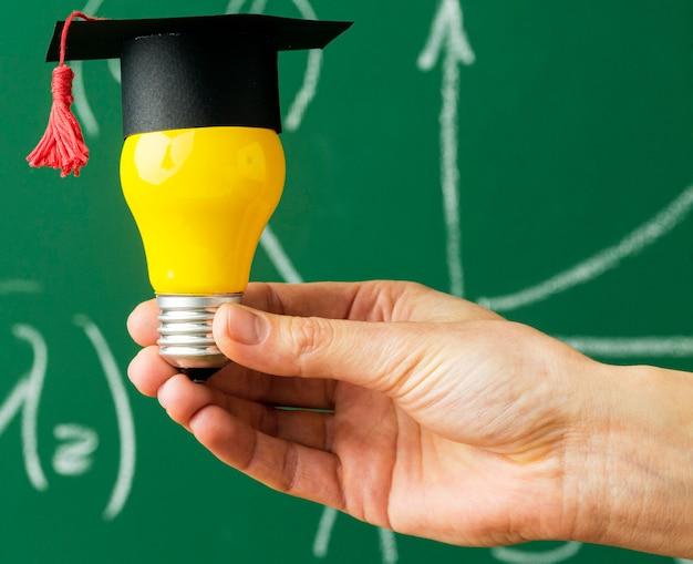 Osoba trzymająca żarówkę z akademicką czapką