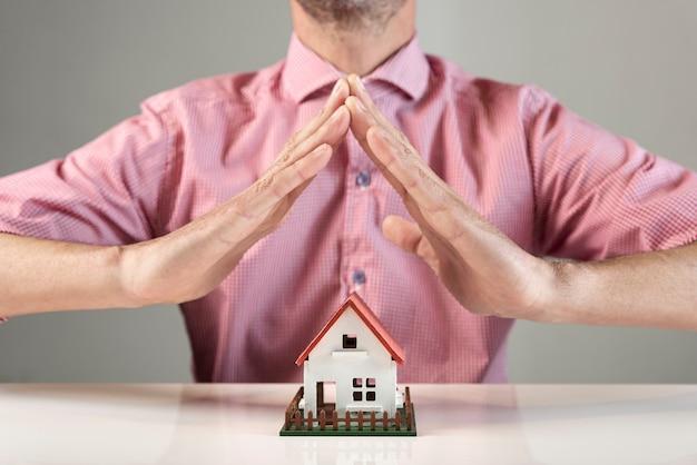 Osoba tworząca dach dla domu rękami