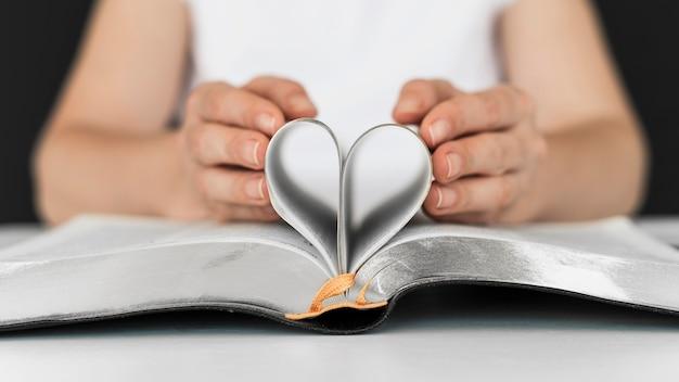 Osoba tworząca serce ze stron świętej księgi