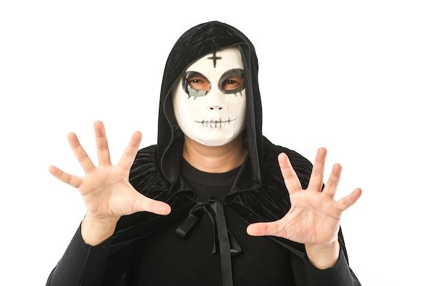 Osoba ubrana w białą maskę z krzyżem na czole i czarnym aksamitnym płaszczem z kapturem, strasząca rękami, na białym tle. koncepcja karnawał, halloween i dzień zmarłych.