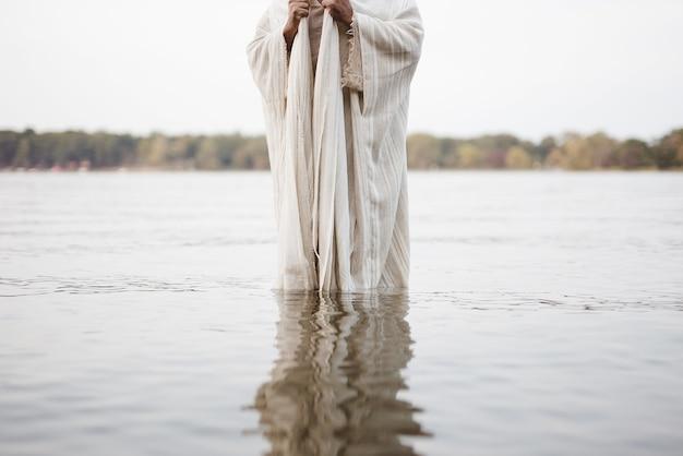 Osoba ubrana w biblijną szatę stojąca w wodzie z zamazaną wodą