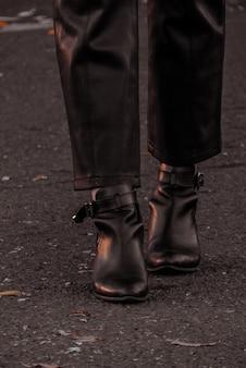 Osoba ubrana w czarne skórzane buty