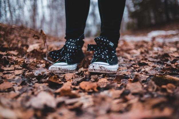 Osoba ubrana w czarno-białe buty stojące na polu ze spadającymi liśćmi na ziemi