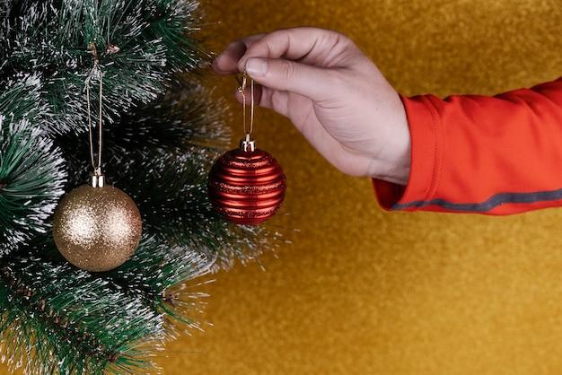 Osoba umieszczająca dekoracje na choince z kulkami w kolorze złotym i czerwonym