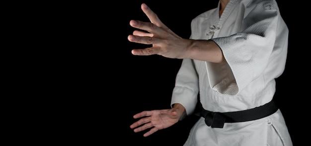 Osoba uprawiająca sztuki walki aikido na czarnym tle.