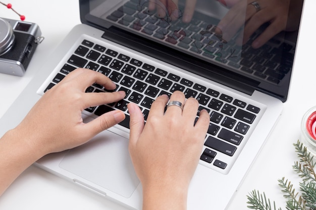 Osoba używa laptop z bożenarodzeniową dekoracją na stole