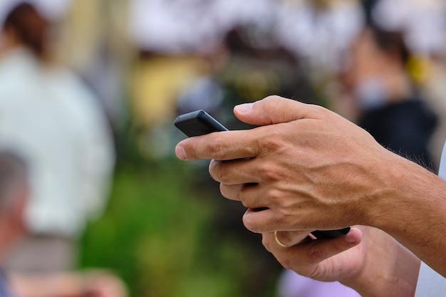 Osoba używa smartfona w mieście latem